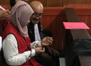 Ayuk alias Puspita, terdakwa perdagangan orang (berjilbab) tengah berbincang dengan seseorang usai menjalani sidang di PN Surabaya.
