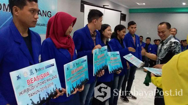 Rektor Dr Nurcholis Sunuyeko memberikan beasiswa secara simbolis pada mahasiswa IKIP Budi Utomo Malang.