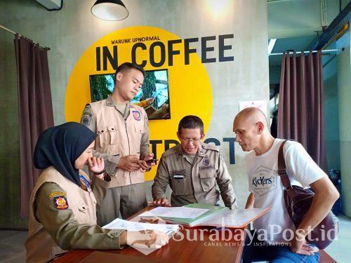 Petugas Satpol PP Pemkot Malang bidang pengawasan, Hariyanto (dua dari kanan) saat memeriksa kelengkapan perizinan cafe Warunk Upnormal dan ditemui oleh Heri Purnomo (kanan) selaku pemilik usaha.