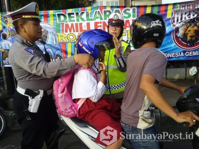 Kanit Dikyasa Satlantas Polres Malang Kota Iptu Muhammad Syakhu mberi helm pada siswa yang takamu pakai helm.