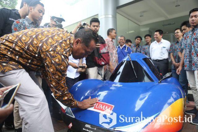 Rektor UMM Dr Fauzan MPd masing stiker pada mobil buatan mahasiswa Fakultas Teknik yang bakal diikutsertakan dalam lomba mobil listrik hemat energi di Sirkuit Sepang Malaysia.
