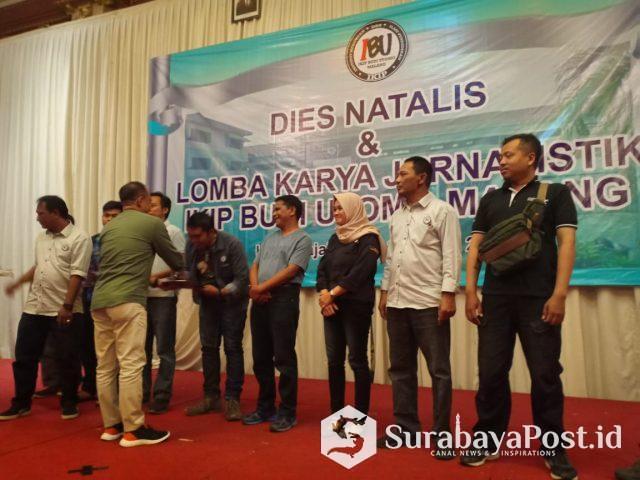 Wartawan SurabayaPost.id, Agus Susanto menerima hadiah dari Rektor IKIP Budi Utomo Malang, Dr H Nurcholis Sunuyeko MSI, sebagai juara pertama dalam lomba jurnalistik kategori media online.