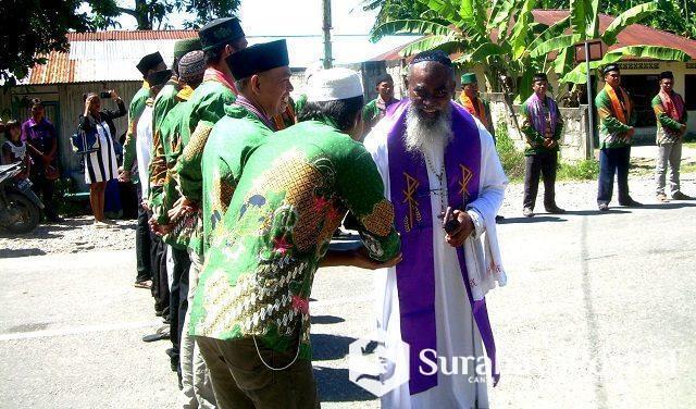 Deken Malaka Romo Edmundus Sako, Pr menyalami para haji dan uztad NU yang terlibat dalam Prosesi Jalan Salib Hidup umat katolik di Betun pada Jumat (19/04/2019).
