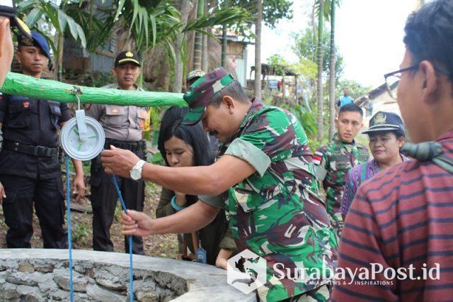 Ketua Tim Dispenda Kol Inf Paiman saat menarik air dari dalam sumur resapan hasil karya Satgas Pamtas RI-RDTL Sektor Barat Yonif Mekanis 741/Garuda Nusantara.
