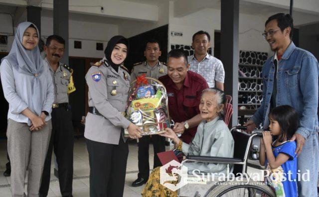 Para perwira Polres Batu menyerahkan bingkisan saatau mengunjungi kediaman warga.
