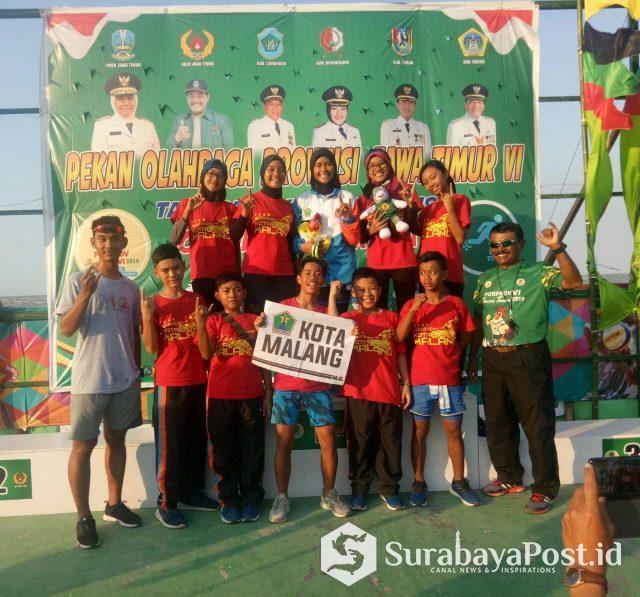 Putri Alisya WD, peraih emas Cabor Sepatu Roda ITT 500 meter putri, pose bersama Tim Kota Malang usai pengalungan medali