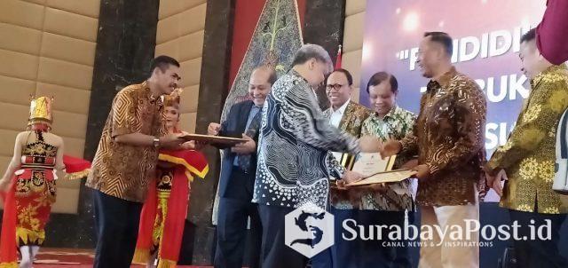 Dirjen Kelembagaan Kemenristekdikti, Patdono menyerahkan penghargaan kepada Rektor UMM, Fauzan