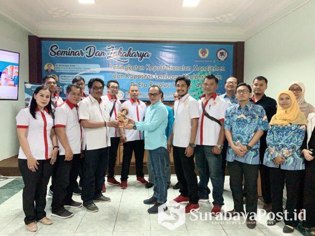 Rektor IBU Malang Dr Nurcholis Sunuyeko saat menyerahkan cinderamata pada Ketua Umum KONI Kabupaten Gianyar, Bali, Pande Made Purwata.